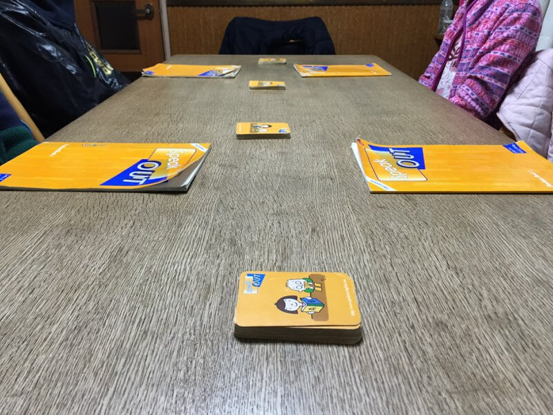 class students with speakout cards and books on table closeup